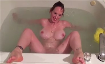 Busty babe masturbates to orgasm with water jet in bath <!-- width=