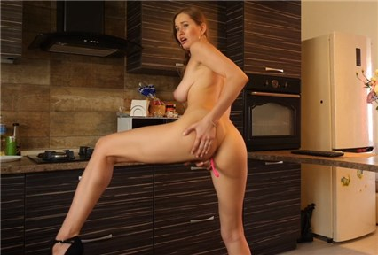 Slender brunette plays with toy in kitchen <!-- width=