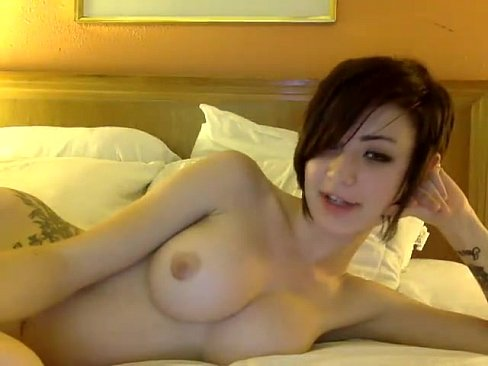 Tattooed short-haired brunette playing with vibrator