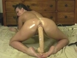 Oiled Brunette with Big Dildo Ride