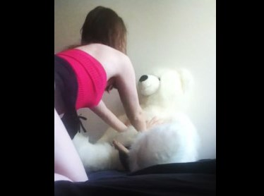 Young girl riding on teddy bear