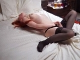 Sexy redhead in black stockings masturbates on bed