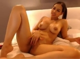 Cute Asian girl with oiled body fingering pussy